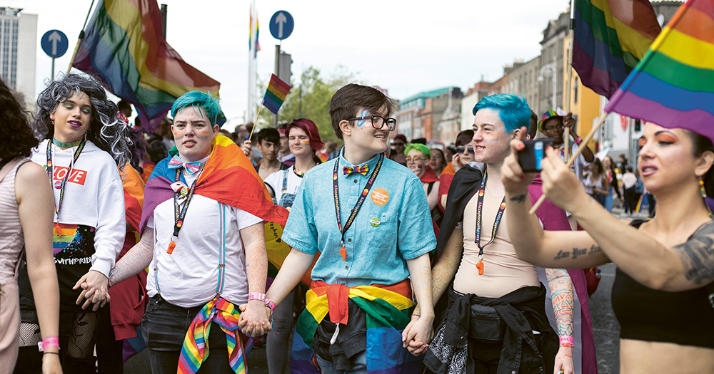 A group of five young people at a Pride Parade, all dressed in rainbow accessories, all holding hands