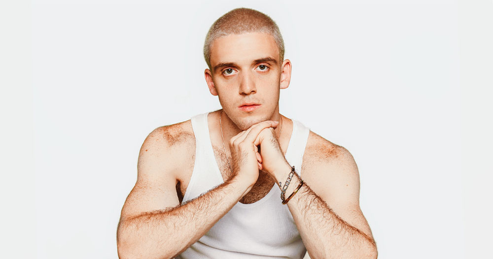 Pop singer Lauv poses with bleached short hair in a vest in front of a blank background