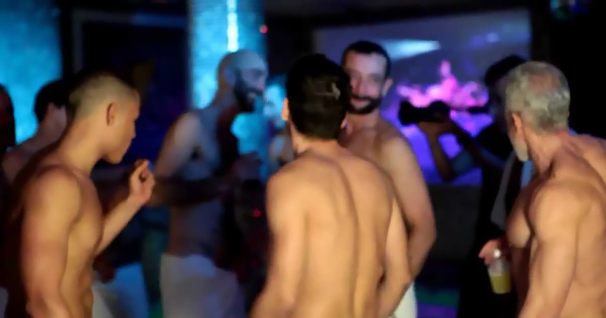 A group of topless men in a nightclub setting