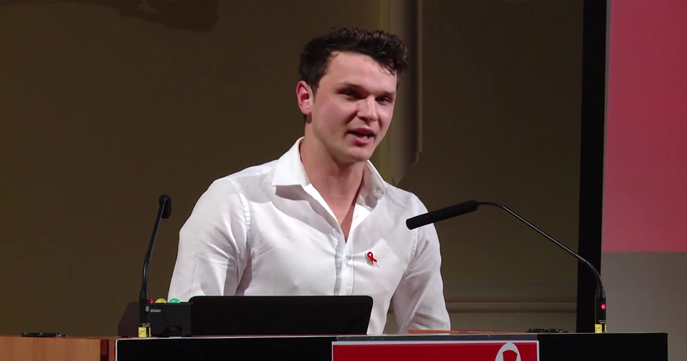 HIV activist Robbie Lawlor standing in front of a podium, speaking. He has just won the Foy-Zappone Award.