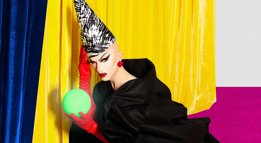 Sasha Velour kneeling on the ground, holding a green crystal ball, promotional image for 'Smoke and Mirrors'