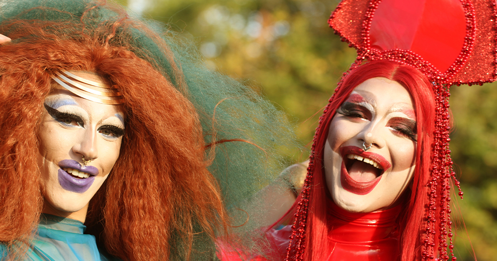 Two drag queens laughing in a park