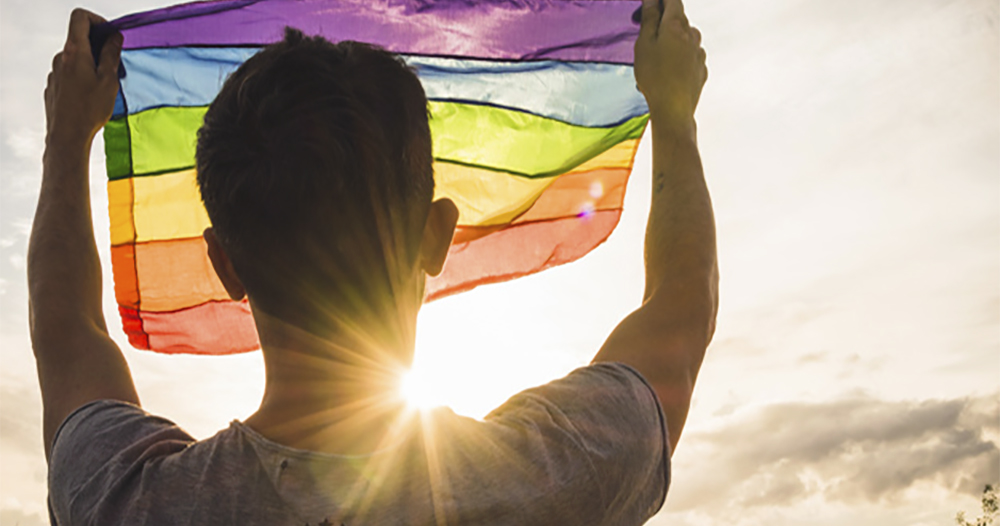 Gay Brazilian man on his self-discovering journey: image of a man from behind holding a rainbow flag while looking at the sunset