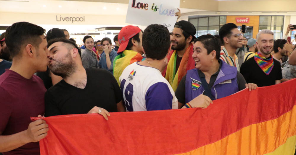 People holding a rainbow flag and kissing each other as part of kiss-in protest at a Mexico mall