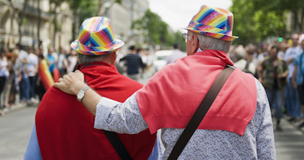 Two elderly men walking down the street, wearing rainbow hats, RTE are looking for people over 65 for new documentary Late Date.