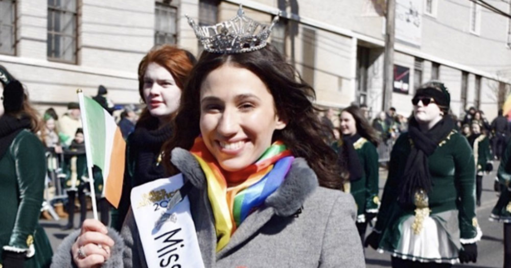 Miss Staten Island in her sash with a rainbow scarf, waving an Irish flag, walks in a parade