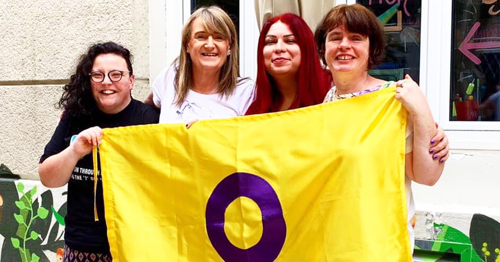 Four Intersex Ireland members smiling while holding an intersex flag
