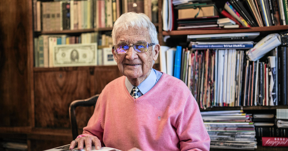 An elderly man in a jumper and glasses smiles at the camera sitting at a desk in his library