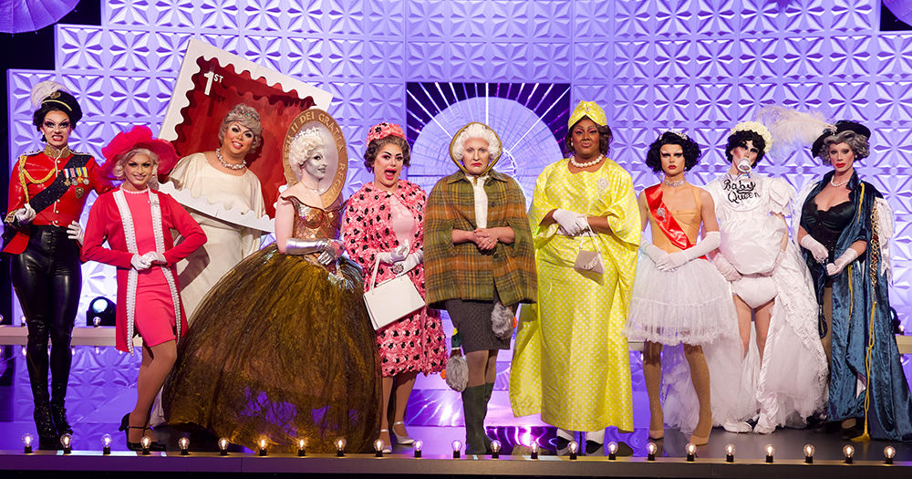 A large group of drag queens on stage dressed as different version of Queen Elizabeth