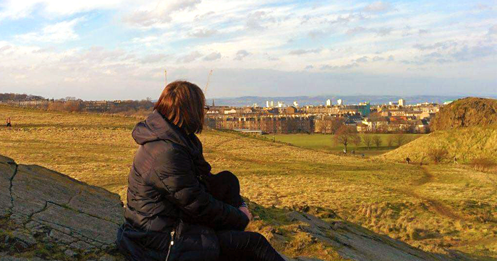 Russian woman sitting at the hill of a park looking at the city in front of her