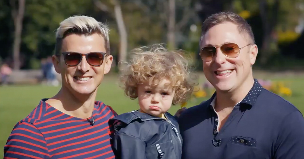 Two smiling men in sun glasses hold a curly headed toddler between them in a park
