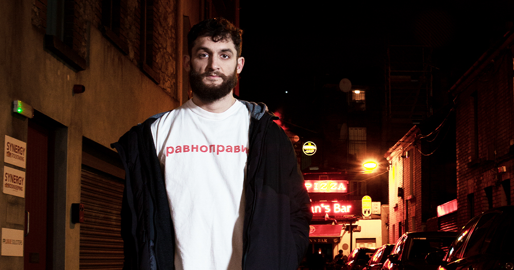 A man with a beard wearing a t-shirt and jacket standing in a dark alley at night