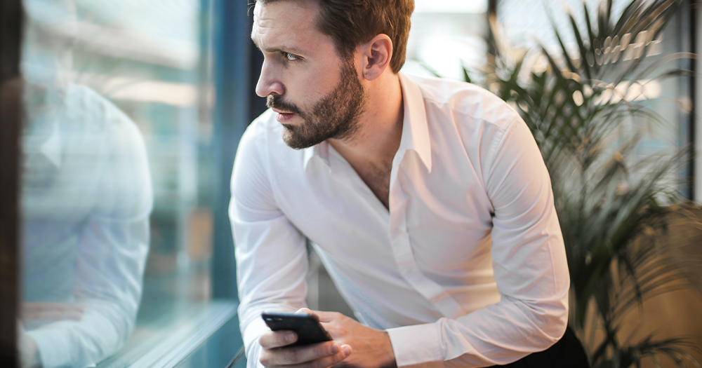 A bearded man in a white shirt looks out a window while holding a mobile phone