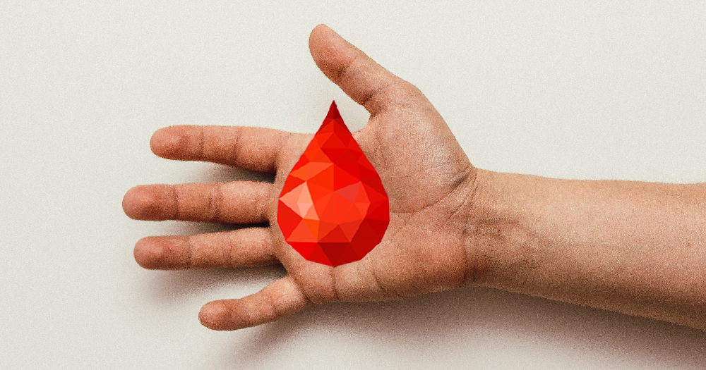A hand holding a red gem in the shape of a drop of blood