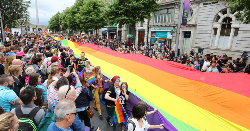 A huge rainbow flag is stretched the length of O'Connell Street by a crowd of people