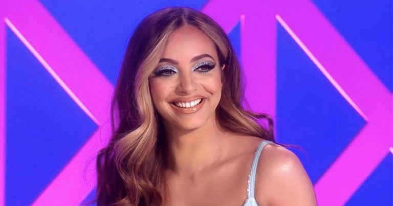 Jade from Little Mix with long wavy hair and strappy dress smiling in front of a multicoloured background