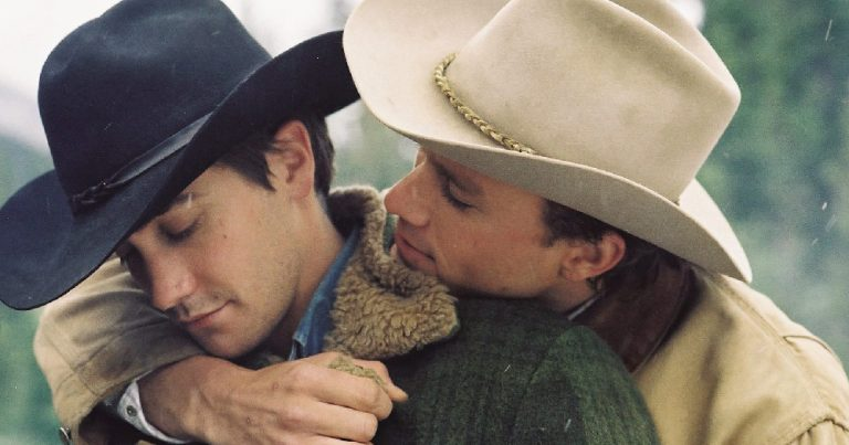 Two men in cowboys hats embracing