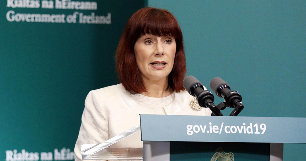 A middle aged woman dressed in white with a bob haircut speaks at a government podium