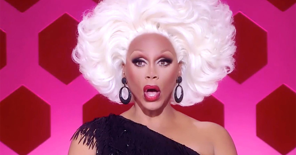 A drag queen in an off the shoulder gown and a huge white wig looking surprised