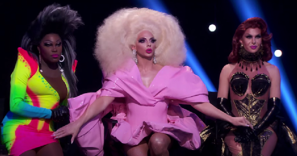 Three drag queens in full costume looking shocked