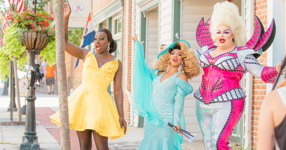 Three drag queens of different races wave from a small town sidewalk