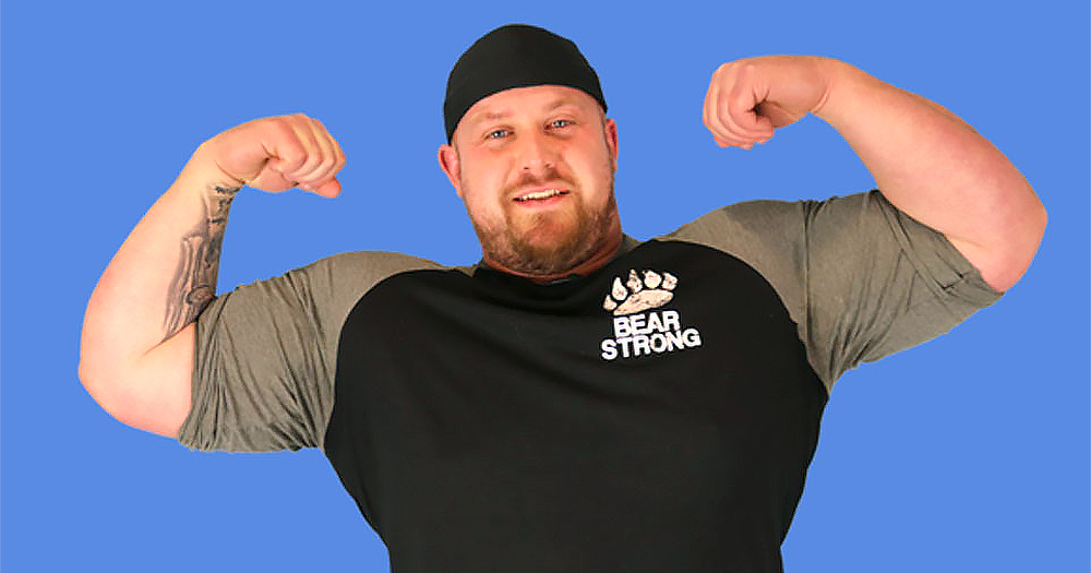 Strongman Chris McNaughton flexing his arms in front of a blue screen