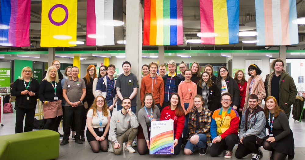 The members of DCU LGBTA society pose under hanging flags representing diversity