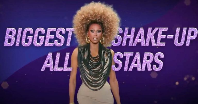 A black drag queen with a huge afro poses in a promo image