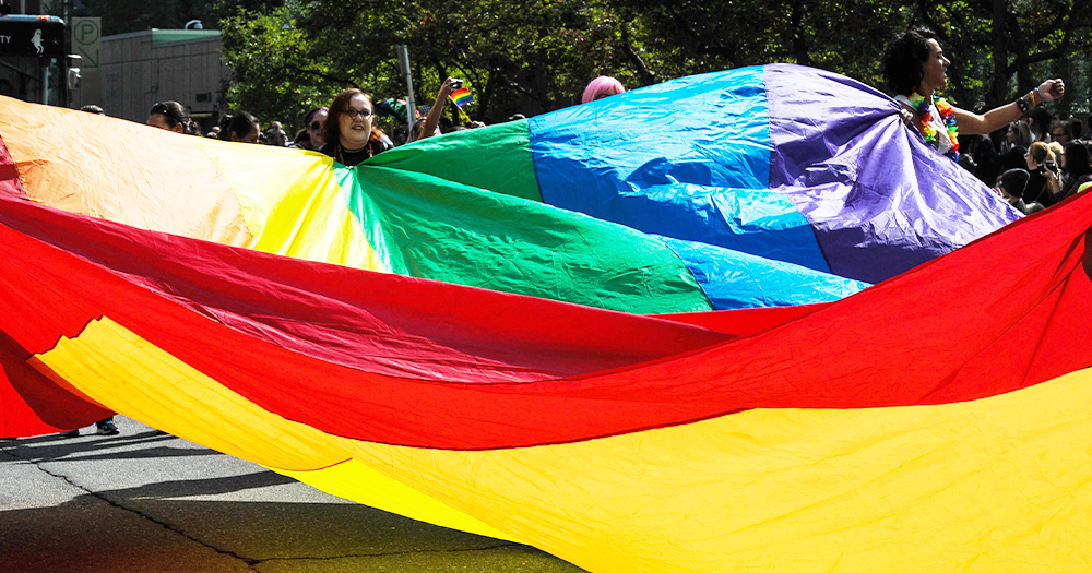 Young people on a city street hold a huge rainbow flag