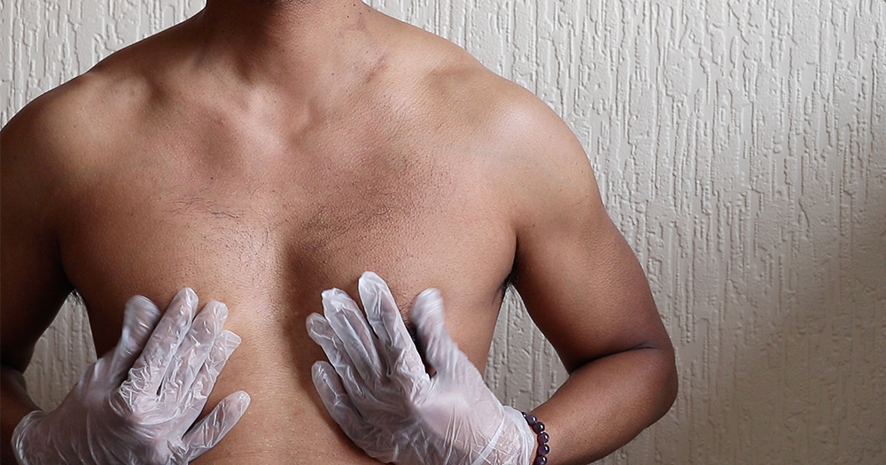 A topless male torso with rubber gloved hands caressing itself
