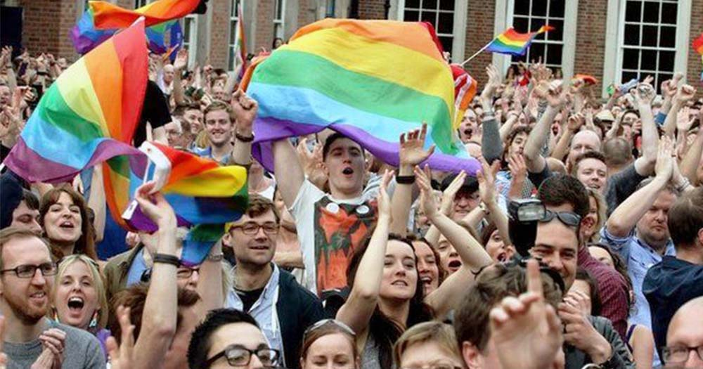 Crowds of people celebrating, holding rainbow flags
