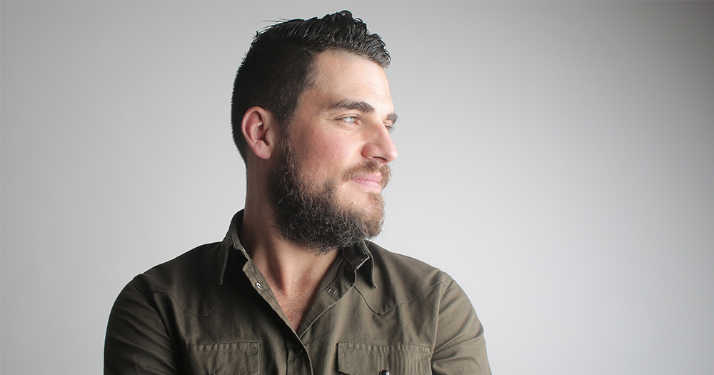 Positive mental health image of a smiling bearded man looking into the distance