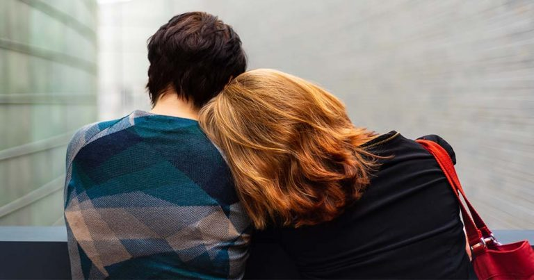 Seen from behind, a woman with long red hair rests her head on the shoulder of a woman with short dark hair