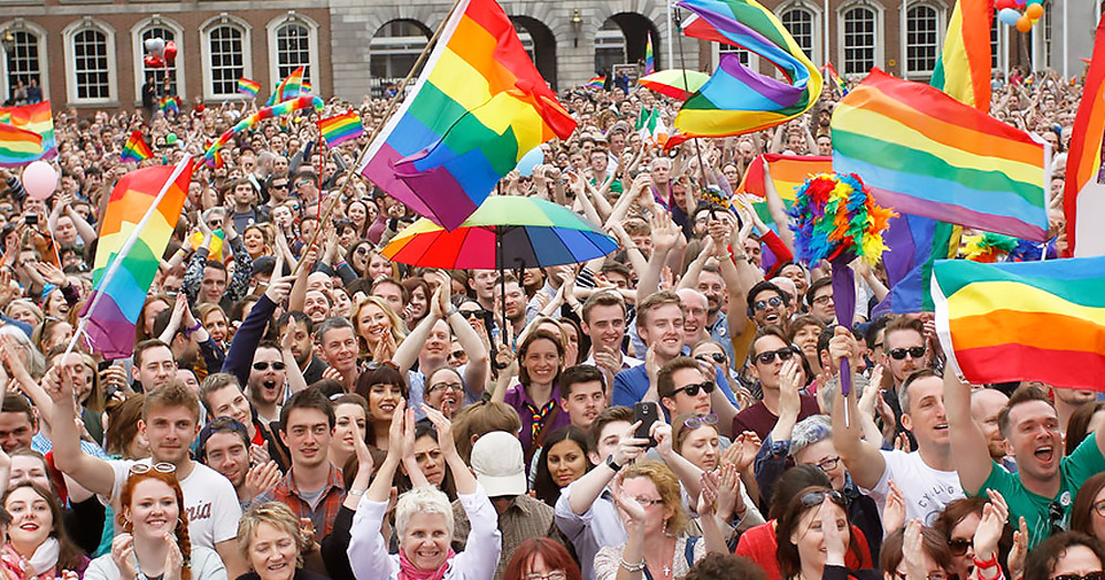 Mar Ref 5 Years On - Crowds of people in Dublin Castle wave rainbow flags
