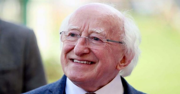 President Higgins, an older man with white hair and glasses, smiles for a photo
