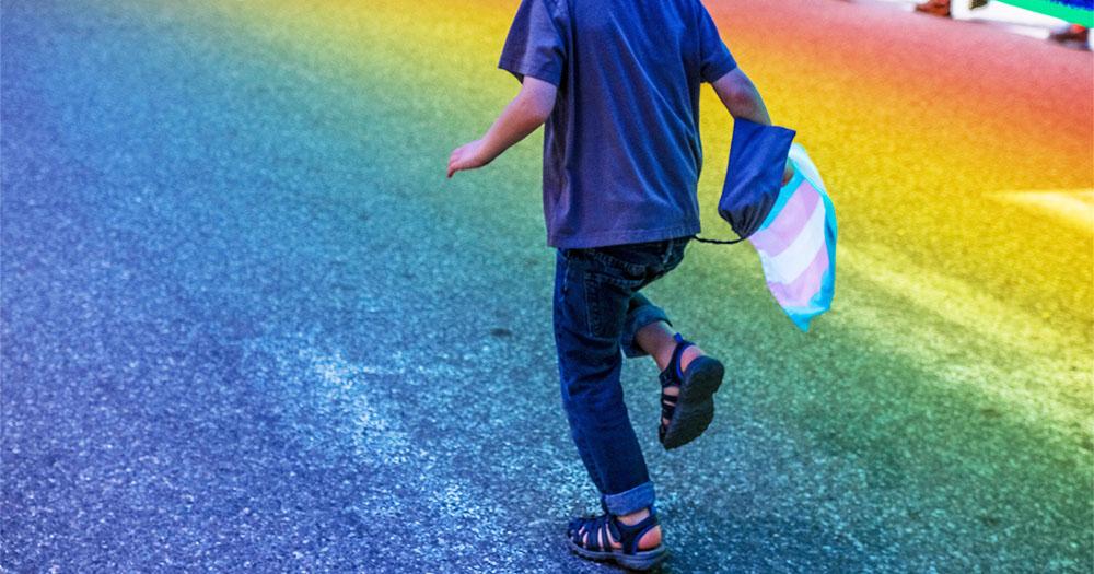 A kid holding a trans flag runs along a rainbow coloured street
