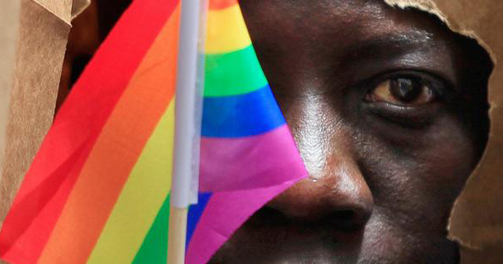 A rainbow flag obscures the face of a young black man