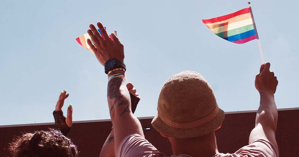 A man wearing a hat and a woman seen from behind both waving little Pride flags