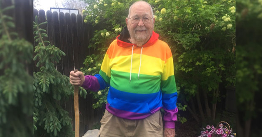 A 90 year old man in a rainbow flag hoodie stands in his garden holding a shovel