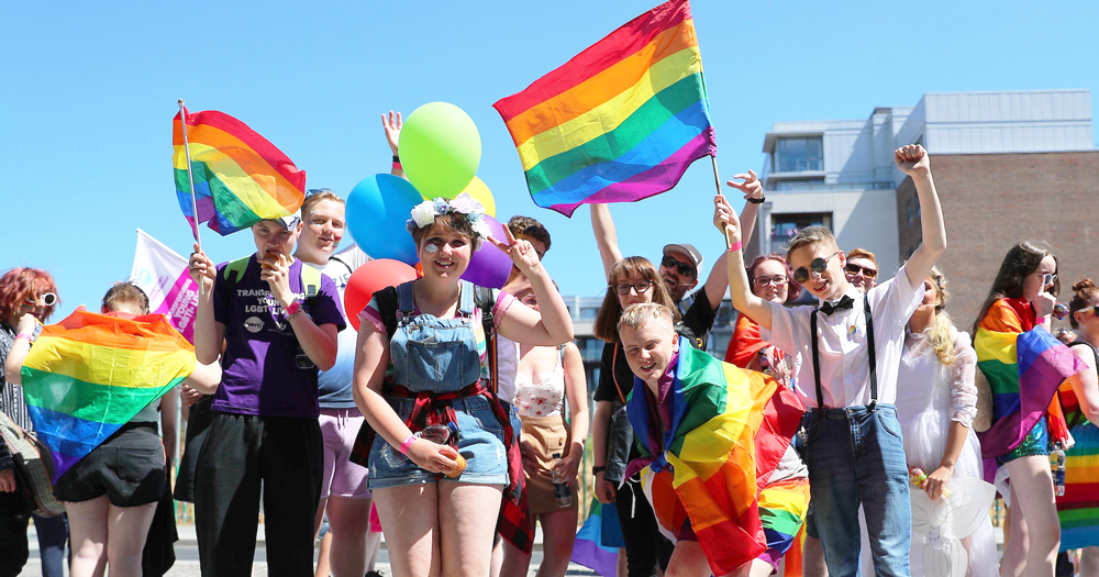 A large group of young people waving rainbow flags
