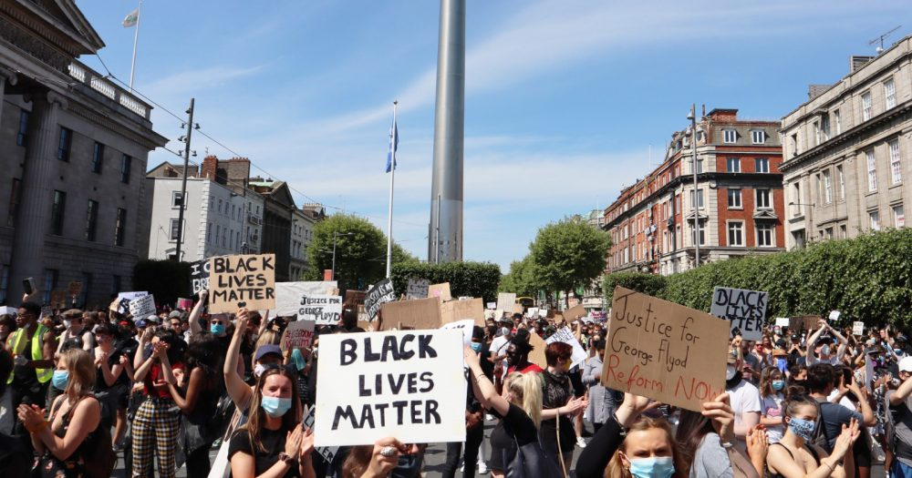 People marching in Dublin while holding signs at the #BlackLivesMatter protest
