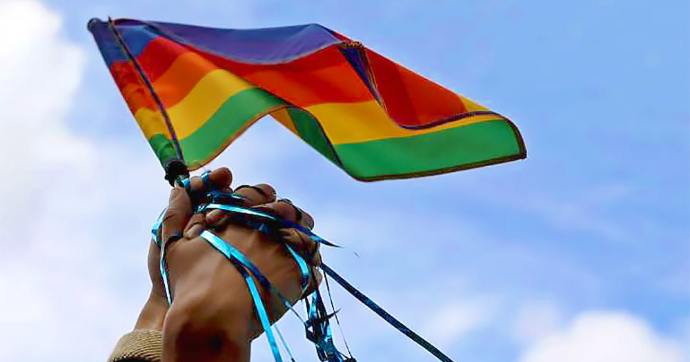 Two hands holding a pride flag. In this story, we interview members of Black Pride Ireland