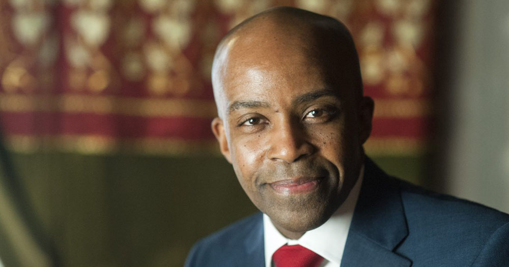 A smiling bald black man in a suit poses for a photo in an office