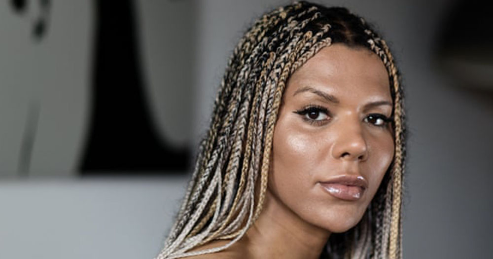 A black woman with long hair in braids looks over her shoulder at the camera