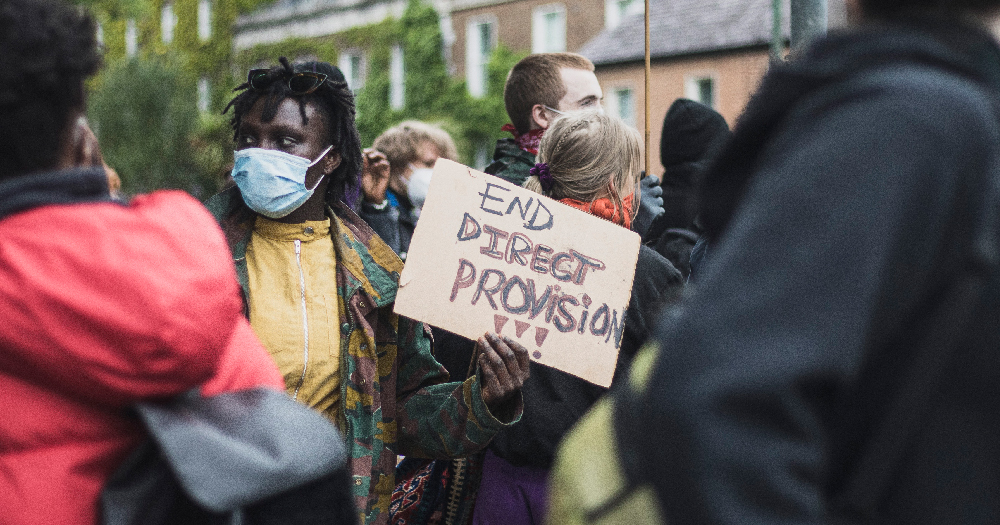 person holds end Direct Provision sign