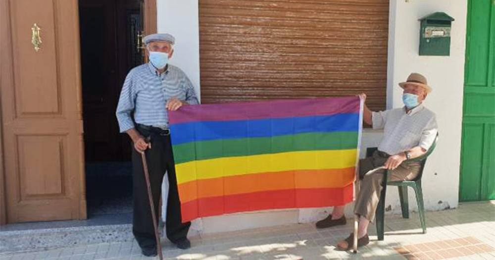 Two elderly men with facemarks hold up a Pride flag