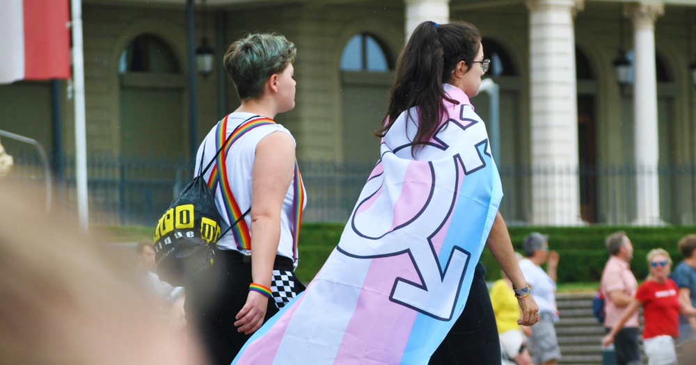 Two young people walking, one wrapped in trans flag