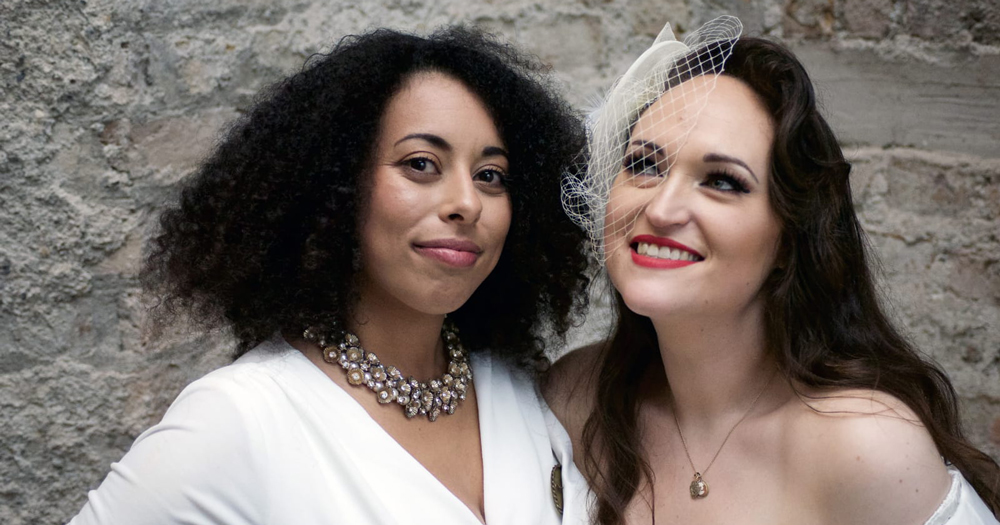A black woman and a white woman wearing wedding dresses