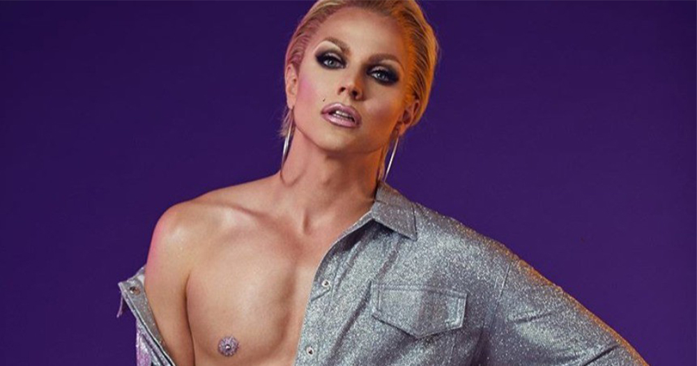 A drag queen with full makeup and an exposed male chest