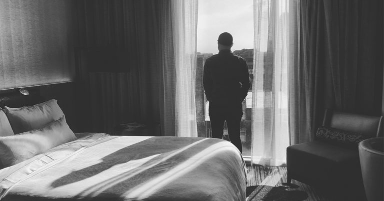 A silhouette of a man standing in the window of a hotel room